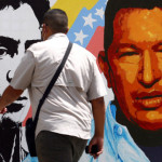 A man in Caracas walks past a mural featuring Simon Bolivar and Hugo Chavez Photo: CNN