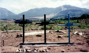Graves of victims of Hurricane Mitch, with the gigantic mud slide visible in the background