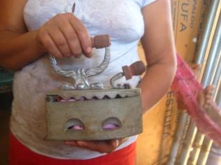 Emilse Senteno displays her old fashioned iron