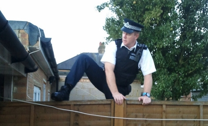 UK policeman jumping over a fence