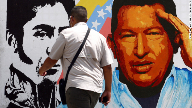 A man in Caracas walks past a mural featuring Simon Bolivar and Hugo Chavez. Photo: CNN