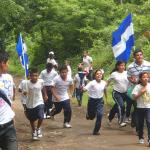 Schoolchildren run through El Pochote carrying the 'Torch of Liberty'
