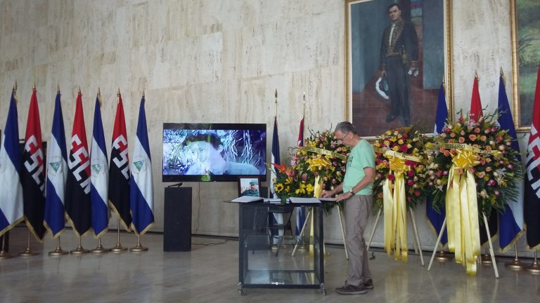 Signing the book of condolences for Fidel Castro in Managua: the flags are those of the Sandinista Front and of the Republic of Nicaragua